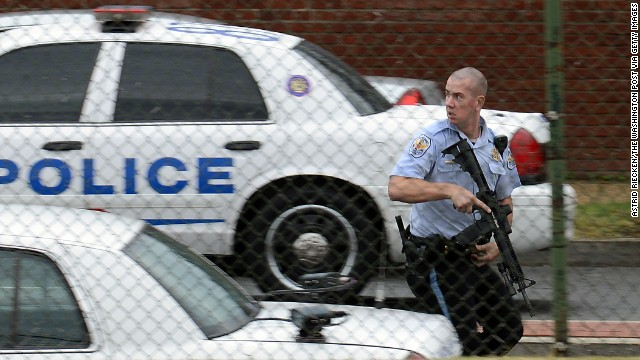 A police officer runs near the scene of the shooting rampage at the Washington Navy Yard on Monday, September 16. Authorities said at least 12 people -- and the suspect -- were killed in the shooting.