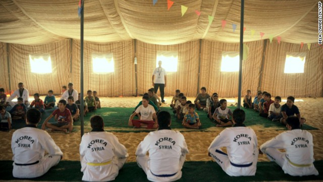 Syrian refugee children watch Korean and Syrian taekwondo instructors during training at the Zaatari refugee camp in Jordan on September 17.