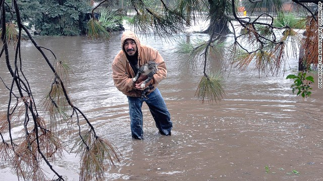 Johnny C. Montoya helps rescue a cat from an area flooded by the Gallinas River in Las Vegas on September 13.