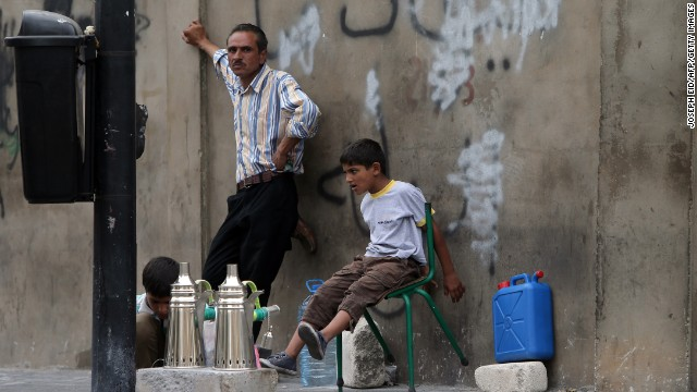 Young Syrian refugees sit with their father as he prepares coffee to sell on a street in Beirut on September 18.