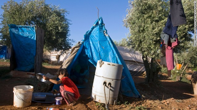 A young Syrian girl washes a pan at the Atme refugee camp along the Turkish border on September 17.