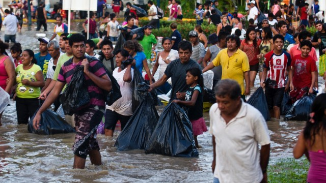 Residents carry goods and supplies in Acapulco on September 17.