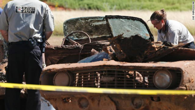 Officials examine one of the cars in September 2013.