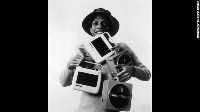 "The cassette was introduced in 1963; the 8-track tape in 1964. Both were portable ways of listening to music. Here, actor Jimmie Walker (as his ""Good Times"" character J.J.) poses with several 8-track and cassette players."