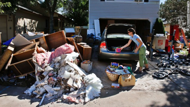 A woman disposes of ruined items from her home in Longmont on Wednesday, September 18.