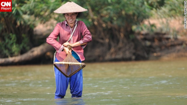 "A smiling woman fishes for the day's catch in northern Laos. L. Craig Smith spent four days visiting various villages of the hill tribe people, who ""received us with open arms,"" he said."