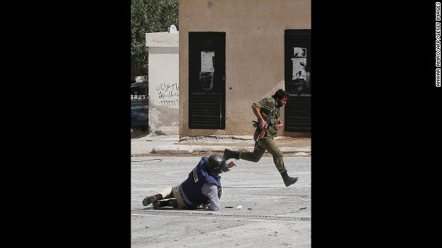 AFP reporter Sammy Ketz hits the ground as a Syrian soldier runs past during sniper fire in Maalula on September 18. Ketz and a photographer were reporting on the ancient Christian Syrian town northeast of Damascus.