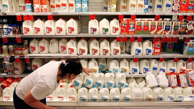 A customer scans the expiration date on gallons of milk sitting at a Safeway grocery store in Washington.