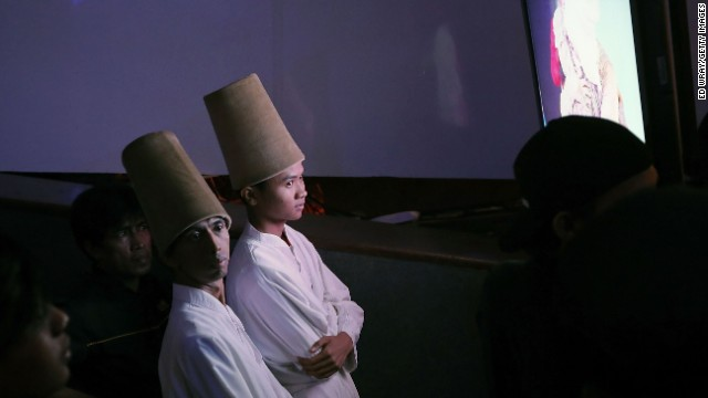 Sufi Muslim dancers watch a monitor offstage during the competition.