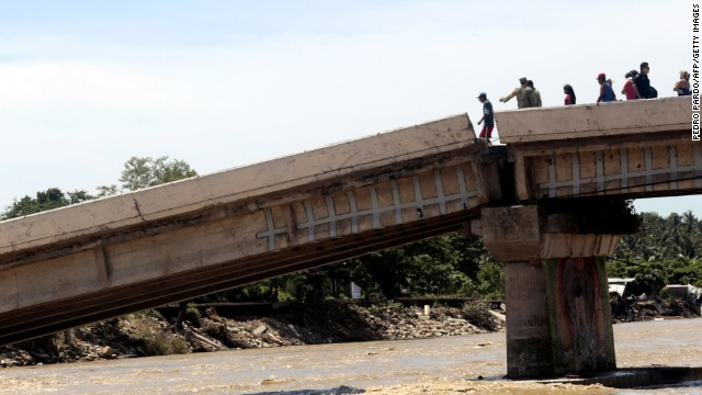 People attempt to cross a collapsed bridge in Coyuca de Benitez on September 18.