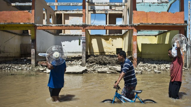 People wade through a flooded street in Acapulco, Mexico, on Wednesday, September 18.