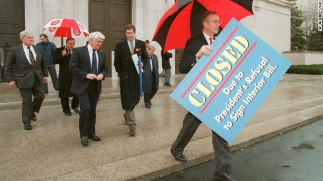 "House Appropriations Committee Chairman Rep. Bob Livingston, right, holds a ""closed"" sign outside the National Gallery of Art in Washington on December 18, 1995."
