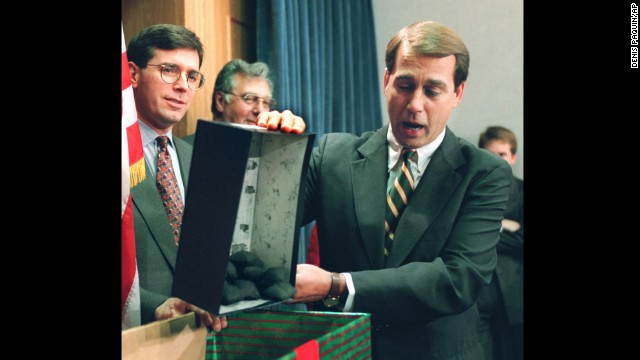 Rep. John Boehner dumps out coal, which he called a Christmas gift to President Clinton, during a news conference about the federal budget on December 21, 1995.