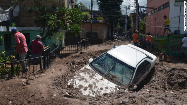 A car lies submerged in mud as residents attempt to clean up.