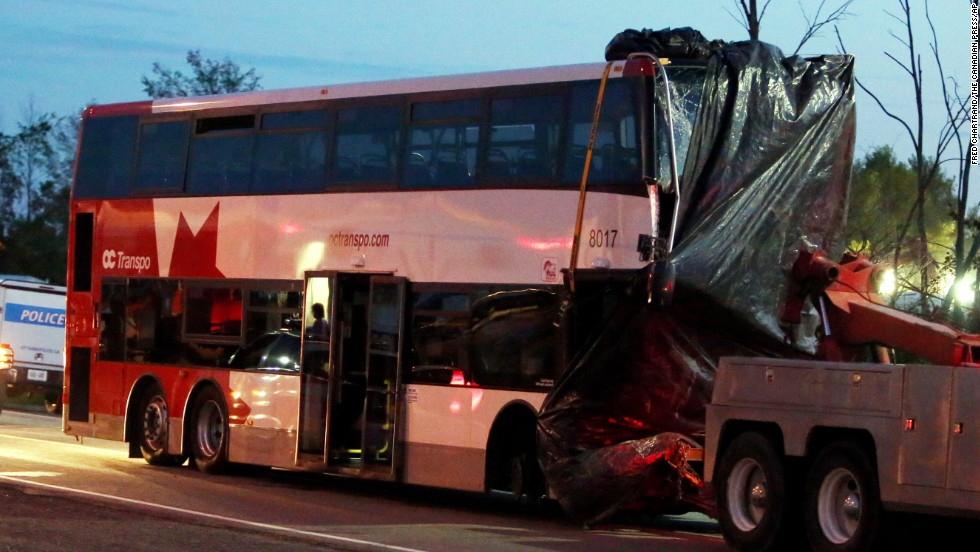 An Ottawa, Ontario, double-decker bus plowed into a moving train on Wednesday, September 18, in a horrific morning crash that left six dead and at least 34 others injured. The bus is towed away from the site of the crash on Thursday, September 19. Click through for more images from the crash: