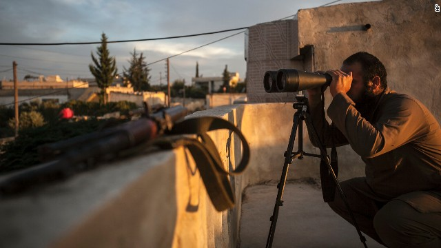 A Syrian opposition fighter watches as heavy fighting erupts in the neighboring village of Kafr Nabuda in the Idlib province on September 19.