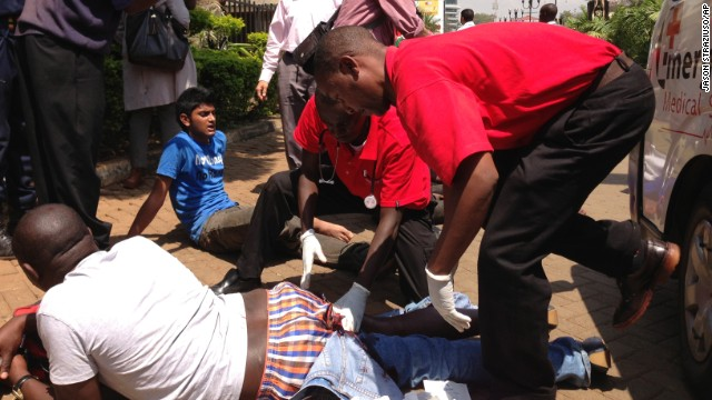 Paramedics treat an injured man outside the mall.