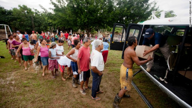 Villagers in San Jeronimo line up at a helicopter from Mexico's Attorney General's Office to get aid on September 20. Federal police have been helping move emergency supplies and bring aid to victims of massive flooding.