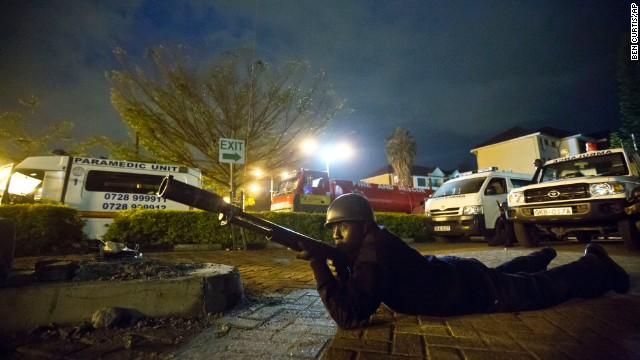 An armed police officer takes cover during a volley of gunfire outside the mall.