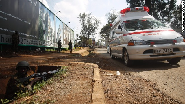Armed Kenyan forces take position to secure the area around the shopping mall as ambulances move in to carry the injured.