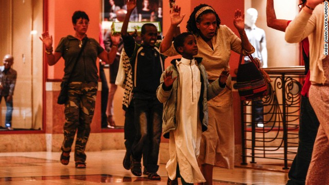 Shoppers run with their arms raised as they exit the mall.