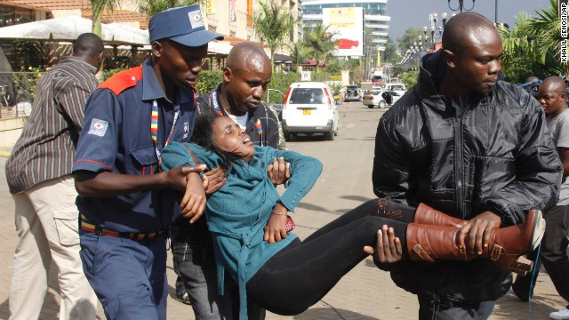 Men help a wounded woman outside the mall.