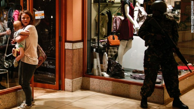 A woman shields a baby as a soldier stands guard inside the Westgate Mall on Saturday, September 21.
