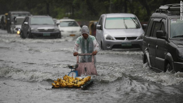 A banana vendor crosses a flooded street on September 22 as monsoon rains from Typhoon Usagi pound Manila, Philippines.
