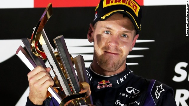 Red Bull's Sebastian Vettel lifts the trophy under lights following his victory at the Singapore Grand Prix, F1's only night race.
