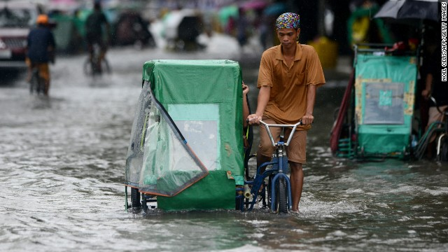 A pedicab driver wades through a flooded street in Manila on Monday.