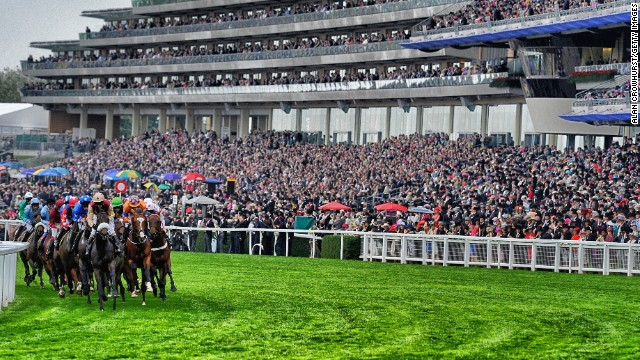 Royal Ascot, Ascot, Berkshire, UK: A packed grandstand watches a tightly-bunched group of runners during a race at Royal Ascot in June.