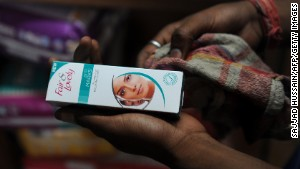 A sales assistant holds Fair and Lovely skin fairness cream at a shop in New Delhi.