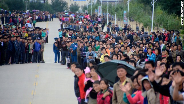 The streets of Rason were lined with thousands of people cheering, waving flags and taking photos with mobile phones.