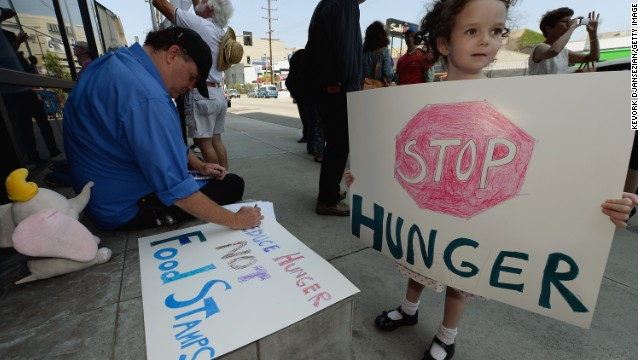 A girl joins her dad and others in June in Los Angeles protesting the farm bill that just passed.