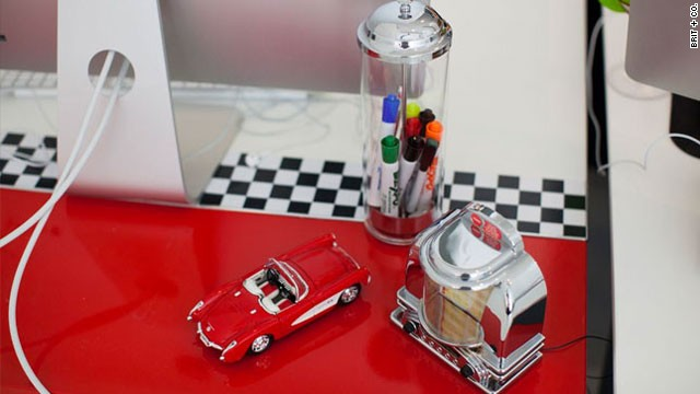 "Brit + Co. sponsored a ""Pimp My Desk"" contest for its employees. Winner Dzuy Linh created a diner-themed desk using 1950s-themed objcts as accessories and vinyl decals to create a red and checkerboard base."