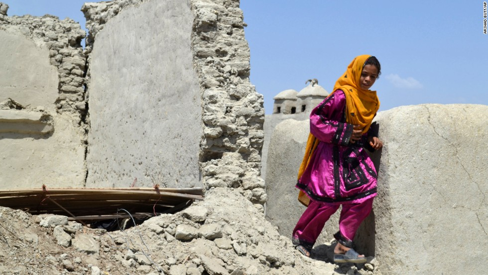 A girl walks past the remnants of a house in the earthquake-devastated district of Awaran on Thursday, September 26. The 7.7-magnitude quake struck on September 24 in a remote, sparsely populated area of southwestern Pakistan.