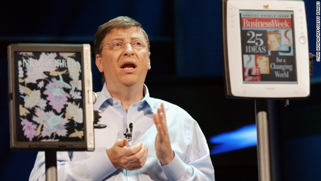 Gates speaks, standing between two models of the Tablet PC, at the announcement of the availability of the devices and Windows XP Tablet PC operating system in 2002.