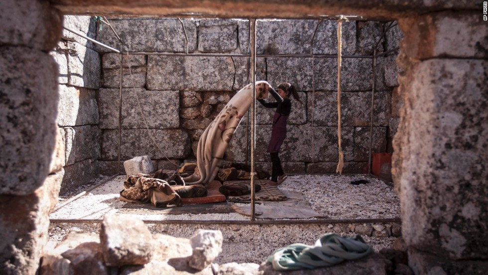 SEPTEMBER 30 - KAFER ROUMA, SYRIA: A displaced girl makes her bed after waking up in ancient ruins near Kafer Rouma, used as a temporary shelter by families who fled from heavy fighting and shelling in Syria's Idlib province. The <a href='http://www.cnn.com/2013/09/03/world/meast/syria-refugees-unhcr/'>U.N. says more than 4 million people are displaced inside Syria</a>, while a further 2 million have been forced to leave the country.
