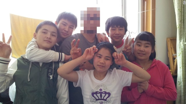 Young North Korean defectors pose for a photo with the South Korean missionary, known only as M.J. , a few days before they departed for the China-Laos border in May. M.J.'s face is obscured for his own safety.