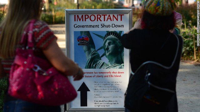 People look at a pointer announcing that the Statue of Liberty is sealed in New York on Oct 1.
