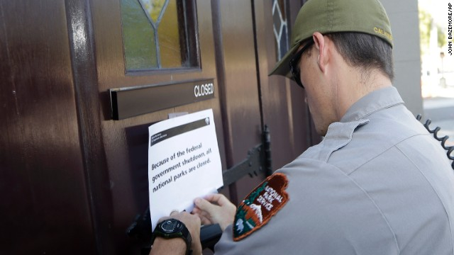 A National Parks Service ranger posts a pointer on the doors of the ancestral Ebenezer Baptist Church in Atlanta on Oct 1 notifying visitors that the church is closed.