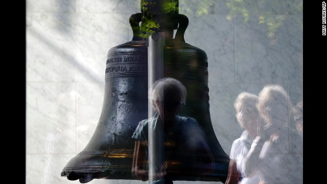 Visitors to Independence National Historical Park are reflected in the window of the sealed building housing the Liberty Bell, on Oct 1 in Philadelphia.