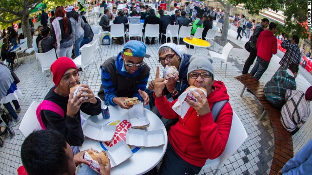 Fast-food fans taste their first Burger King meal from the newly opened Cape Town restaurant, in May 2013.