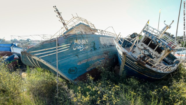 Weather-beaten boats once used by illegal immigrants to arrive on the Italian island of Lampedusa lay in the harbour.