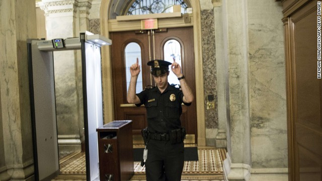 A Capitol Police officer directs people away from a door on Capitol Hill.