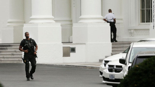 A member of the Secret Service counterassault team walks past the entrance of the White House.
