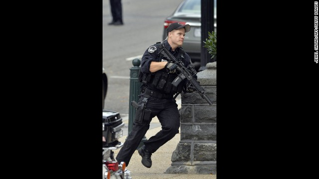 A police officer runs after reports of shots being fired.