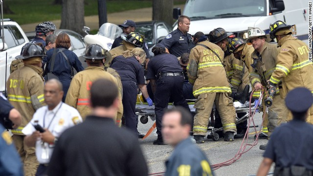 First responders put a police officer on a stretcher after pulling him out of a wrecked cruiser.