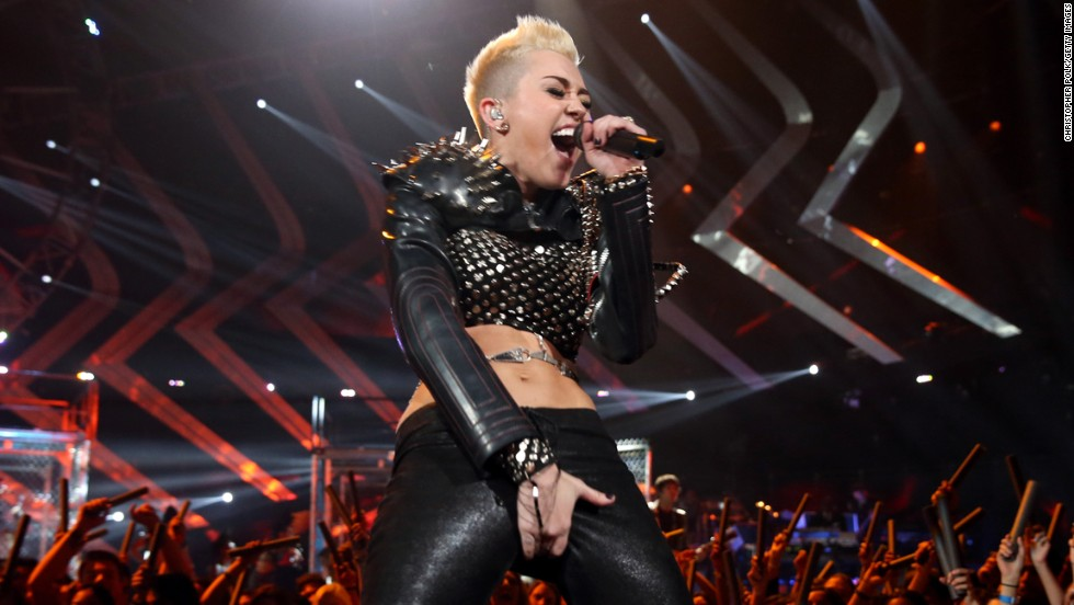 "Miley Cyrus isn't Hannah Montana anymore. These days Cyrus is becoming known for wearing revealing outfits and posing with her tongue out. Here, Cyrus grabs her crotch during the ""VH1 Divas"" 2012 at The Shrine Auditorium in Los Angeles, on December 16, 2012."