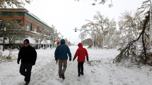 People walk down snow-covered streets in downtown Rapid City, South Dakota, on October 5.